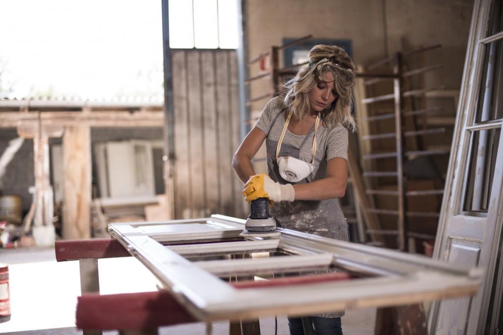 Female carpenter using power sander
